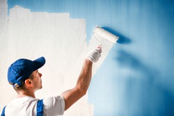 Painter painting a wall with paint roller. Builder worker painting surface with white color.