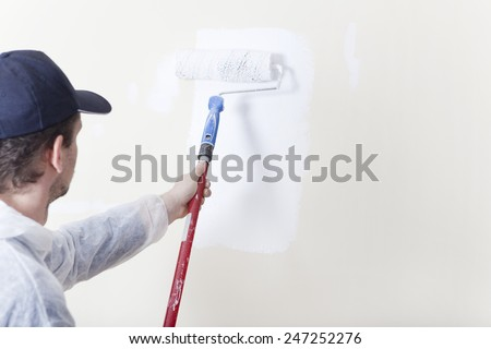 Painter paints an old wall with a paint roller in white
