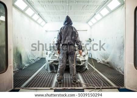 painter posing in front of the booth before painting a car #1039150294