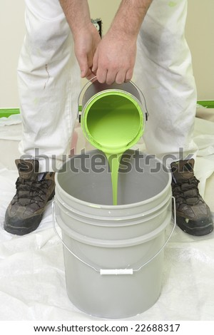 painter pouring green paint into a large bucket
