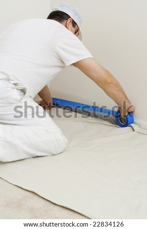 painter protecting the trim with blue masking tape