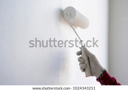 painter roller by construction worker in new cement wall