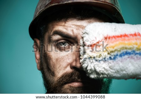 Painter with painting roller. Professional painter worker in protective helmet. Bearded decorator holds paint roller. Male house painter worker. To make repairs. Professional workman in hard hat.