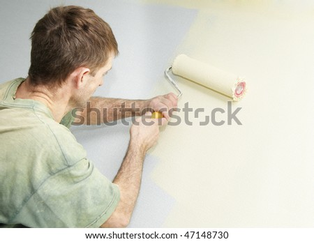 Painter worker hand at decoration work painting a wall with roller