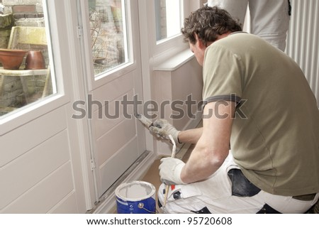 Painter working at door with white paint