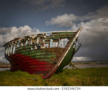 Painterly image of a derelict fishing boat stranded on an Irish beach deteriorating with the help of the changing weather.