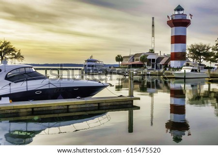 Painterly waterscape of marina and lighthouse near sunset on Hilton Head Island, South Carolina, USA, with digital painting effect, for coastal, marine and travel themes
