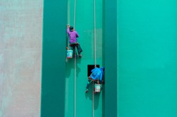 Painters hanging outside of a high building