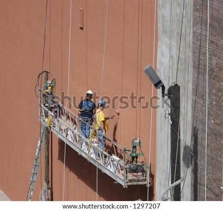Painters on the side of a building with copy space for text