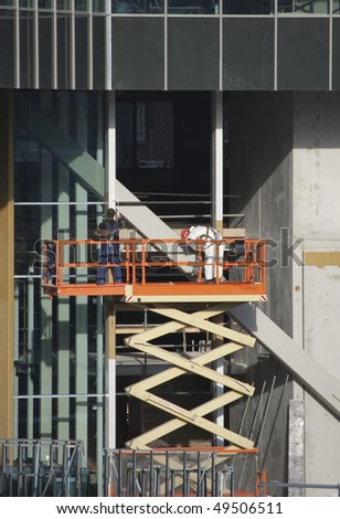 Painters wearing safety harness on a scissor lift