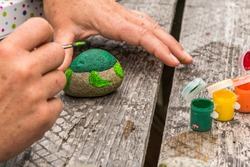Painting a rock green turtle