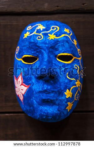 Painting blue mask as subject on wooden background