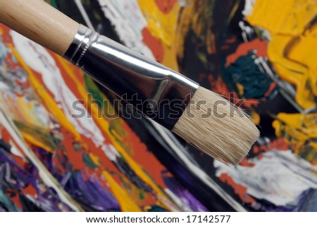 Painting brush over abstract colored background