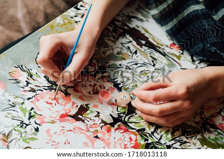 Photo of  Painting by numbers concept. Young girl enjoying coloring picture by numbers. Creative hobby. Leisure activity at home during self-isolation COVID-19