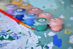 Painting by numbers, creative hobby. Small jars filled with paint on a painted canvas. DIY set with canvas, paints in different colors and brushes. Closeup, selective focus