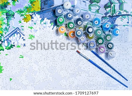 Photo of  Painting by numbers. Set to paint the picture, includes a canvas, paints of different colors, brushes. Top view.