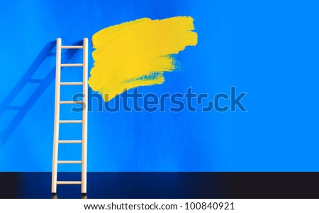 Painting concept. Wooden ladder near blue wall with yellow spot of paint. Nice background