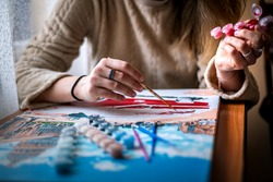Painting for beginners, a woman draws a picture by numbers with acrylic paints on canvas,painting a picture with a brush, a girl draws a picture, self-isolation, home hobby, creativity at home