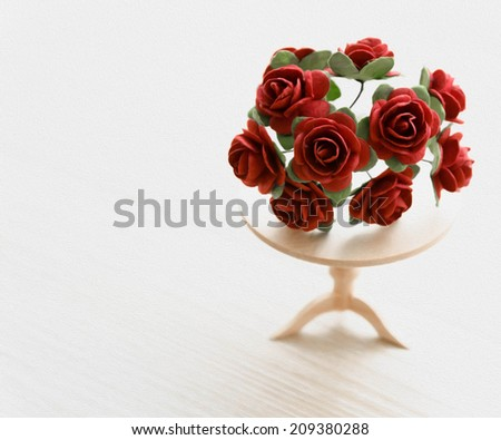 painting miniature red roses on a wooden table. beautiful small world