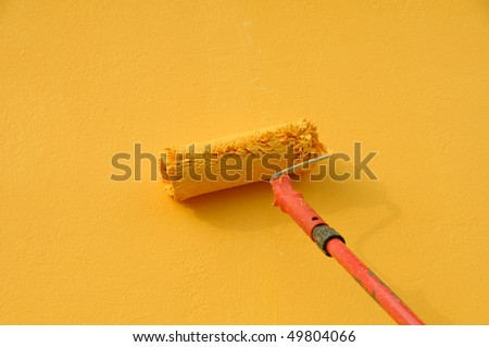 Painting of orange wall with paint roller - stock photo