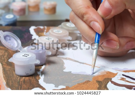 Painting on canvas by numbers. A woman is holding a brush and drawing it. Numbered containers with paints and brushes on the canvas background. #1024445827