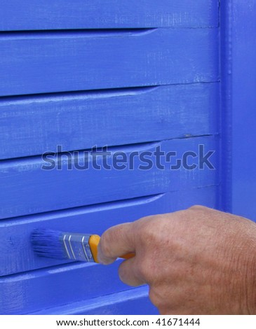 Painting shutters blue - stock photo