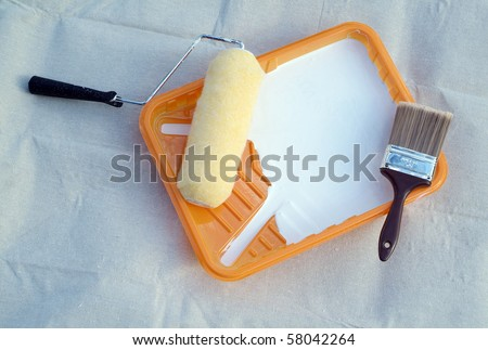 Painting supplies - paint roller and brush in orange tray liner on top of a canvas drop cloth