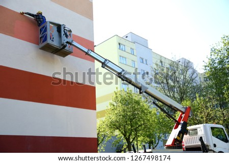 Painting the facade from at a height using a special jib. #1267498174