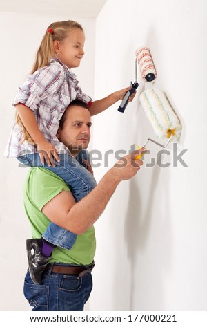 Painting the room with dad - little girl using paint roller playing piggyback with her father
