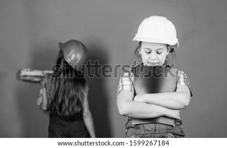 Painting wall. Foreman inspector. Repair. engineering idea. Future career. Little kids in helmet with roller. Labor day. 1 may. small girls repairing together in workshop. relax ar work place.