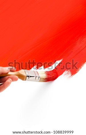 Painting with red colored ink and paintbrush on white