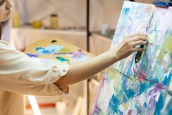 Painting woman. Art process. Abstract artwork. Hobby leisure. Inspiration muse. Unrecognizable pretty lady creating on canvas with colorful oil paints and palette knife.