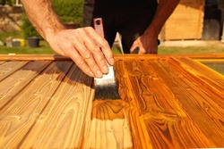 Painting woodwork outside in spring. Close-up of Male hand varnishes a door with a brush. Concept of renovation works, Carpentry details with woodwork and handyman. liquid wood preservative stain