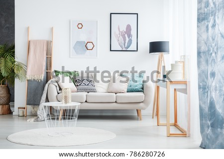 Paintings of cactus and hexagons hanging over a cozy sofa with many pillows standing next to a black lamp in living room interior #786280726