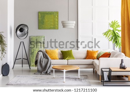 Paintings on the wall and industrial lamp in the corner of elegant living room interior with golden lime accents, real photo with copy space #1217211100