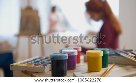 Paints and art supplies in front of artists performing artistic etude witn naked model #1085622278