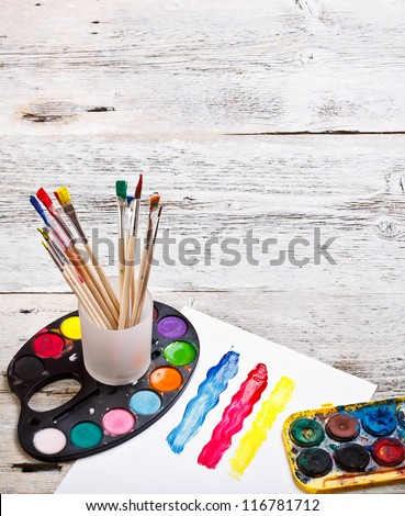 Paints and brushes on a wooden background