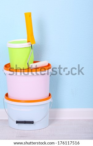 Paints and roll on floor in room on wall background