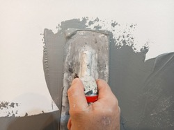 Paints Walls Interior. paint On Wall. paint grey color On the wall. a knife paint in hand With Paints Metallic