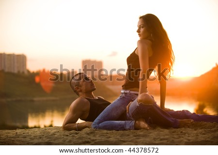 Pair in jeans on a sunset