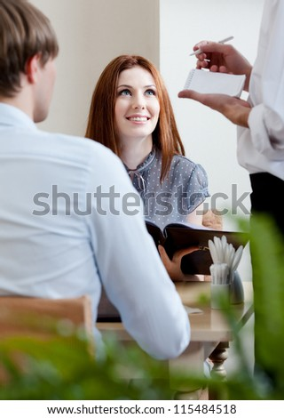 Pair makes the order to the waiter at the cafe