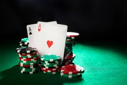 Pair of aces and poker chips on green table.