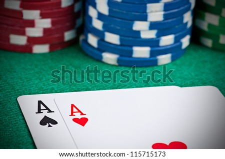 Pair of aces on a poker table with poker chips next to them