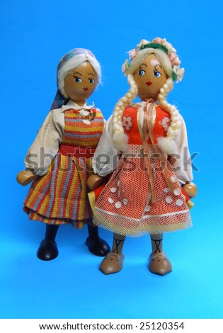 Pair of antique Polish girl dolls on blue background - stock photo