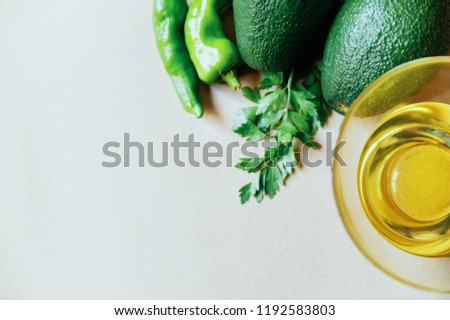 Pair of avocados with an oil in a cup of glass over a brown background above view selective focus selective focus #1192583803