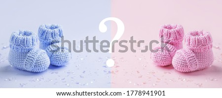 Pair of baby booties, shoes on the blue and pink background, cozy conceptual idea. Guess gender of the child, baby shower party. Preparation and choice of color for newborn baby room