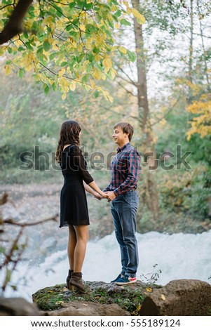 pair of beautiful brunette with a guy holding hands in nature at the waterfall fall trees #555189124