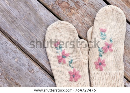 Pair of beautiful female mittens. Women knitted white gloves with a flowers embroidery on old wooden background. Cute present for New Year. #764729476