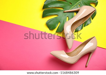 Pair of beautiful shoes with monstera leaf and space for text on color background, top view #1168486309