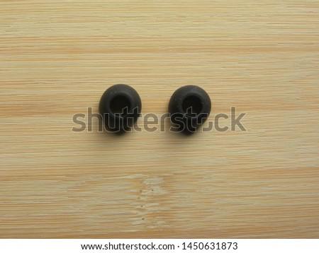 Pair of black color earphone pads of in-ear earphones kept on wooden table